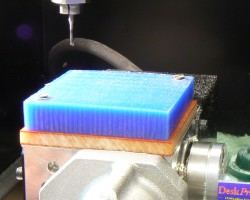 Blue wax block, fixtured on the working area using two screws